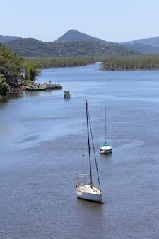 Veleros anclados en tranquilas aguas azules en la desembocadura del río