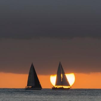 Veleros en el océano al atardecer, waikiki, honolulu, oahu, hawaii, estados unidos