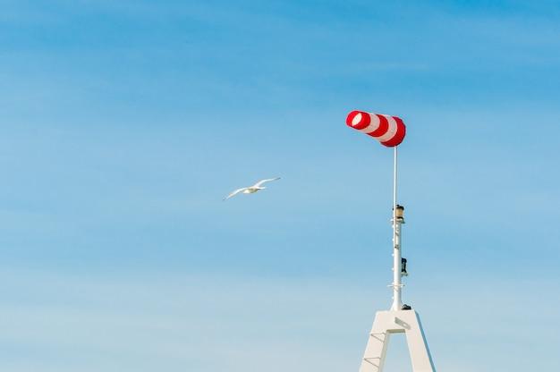 Veleta de manga de viento volando horizontalmente con cielo azul. grandes aves gaviotas volando alrededor.