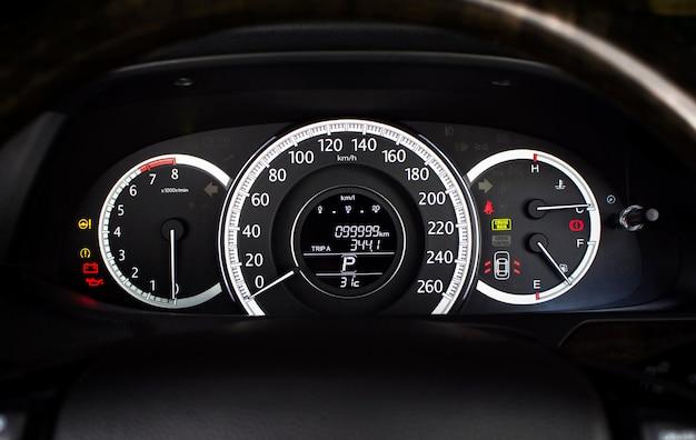 Velocímetro de automóvil con kilómetro por hora y tacómetro, medidor de combustible, odómetro y luz de advertencia en el tablero de instrumentos de un automóvil.