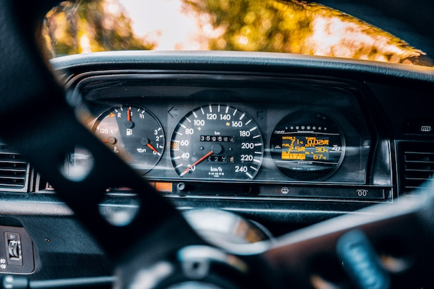 Velocímetro y medidor de consumo de combustible de un automóvil detrás de la rueda de control de dirección