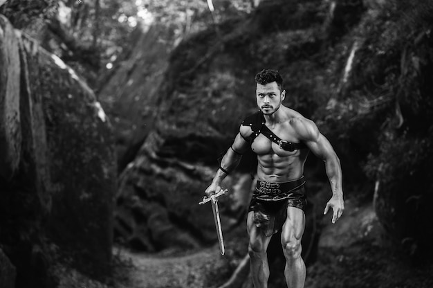 Ven a mi disparo monocromo de un joven gladiador varonil sosteniendo una espada lista para luchar cerca de las rocas