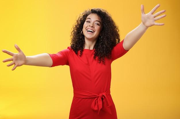 Ven a mis brazos. retrato de mujer encantadora amable y cariñosa, cariñosa con cabello rizado en vestido casual rojo extendió las manos como queriendo dar un abrazo sonriendo ampliamente a la cámara dando una cálida bienvenida o abrazo.