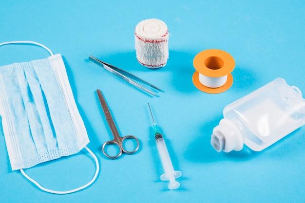 Vendaje ortopédico; pinzas; máscara; jeringa y botella iv sobre fondo azul