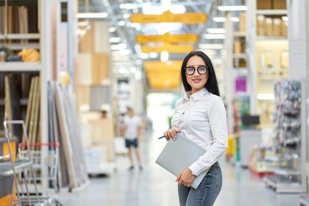 Vendedor atractivo joven atractivo de la muchacha en el centro comercial. vendedora en construcción super store. copia espacio