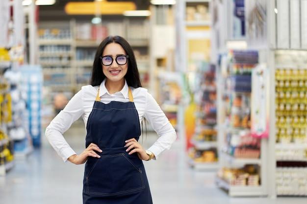 Vendedor atractivo joven positivo en el fondo del centro comercial