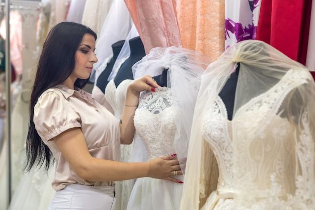Vendedor atractivo en salón nupcial con vestidos de novia