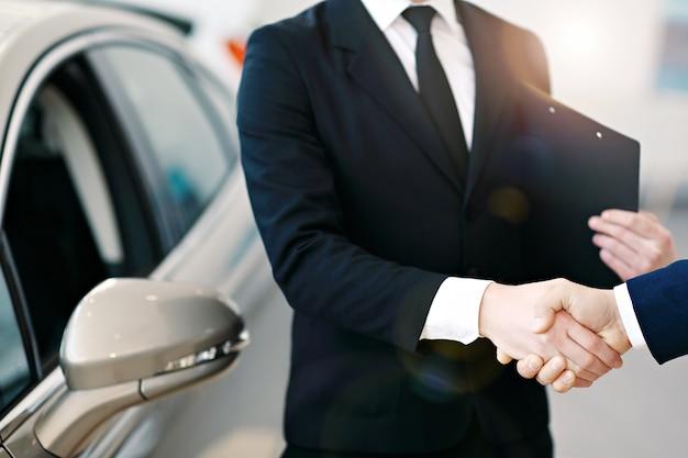 Vendedor de automóviles y apretón de manos del cliente en un concesionario de automóviles