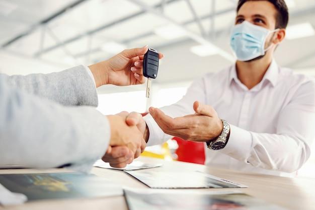 Vendedor de autos dándole la mano al cliente y entregándole las llaves del auto mientras está sentado en el salón del automóvil durante el virus de la corona.