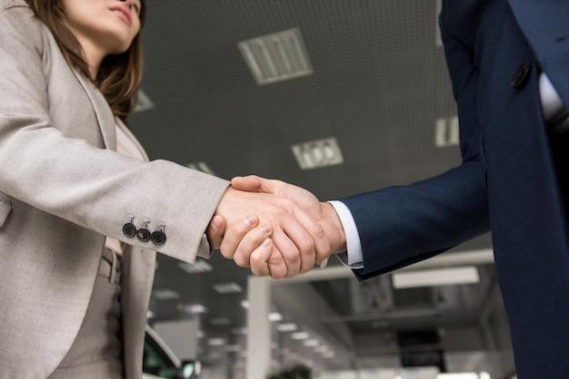 Vendedor de autos estrechándole la mano al cliente