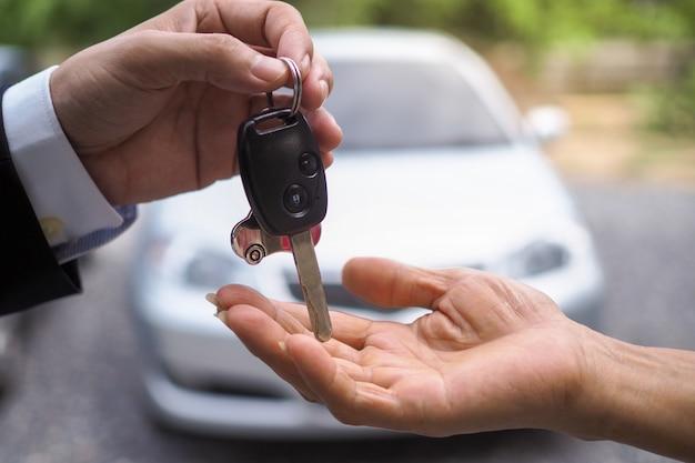 El vendedor de autos y la llave del nuevo dueño.