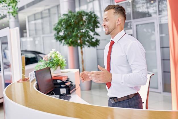 Vendedor caucásico agradable da la bienvenida a los clientes en el concesionario