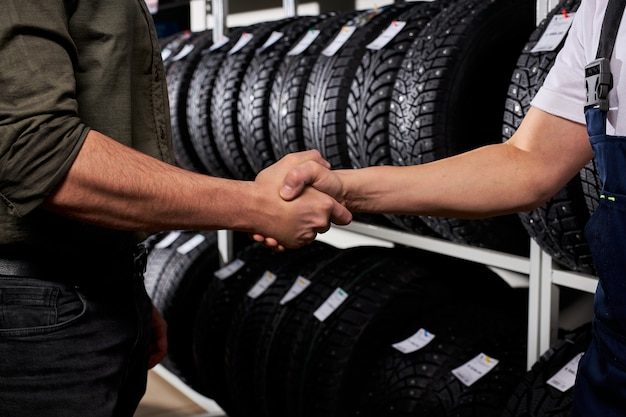 Vendedor y cliente recortada estrecharme la mano con el telón de fondo de los neumáticos de coche. realizar la compra después de elegir el mejor
