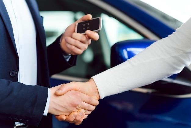 Vendedor de coches entregando las llaves de un coche nuevo a un joven empresario