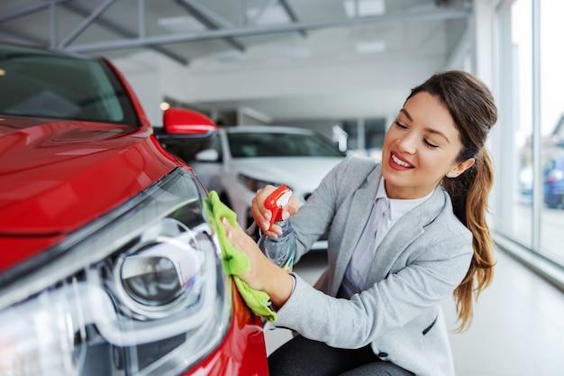 Vendedor de coches femenino ordenado sonriente frotando el coche con detergente y paño. todo debe estar brillante y limpio.