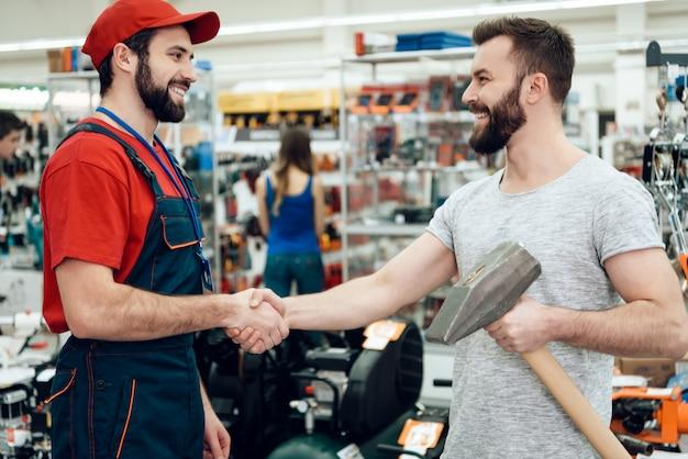 El vendedor está dando al cliente barbudo nuevo martillo gigante.