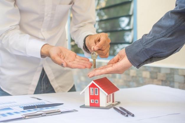 Vendedor dando llave de la casa al cliente en concepto negocio préstamo finanzas inversión familia alquiler seguro