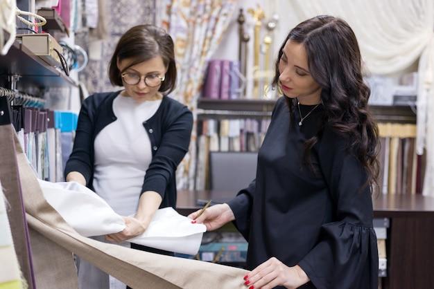 Vendedor - el diseñador textil aconseja a la mujer compradora