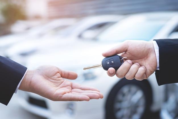 El vendedor entrega las llaves del auto nuevo al cliente en la sala de exhibición.