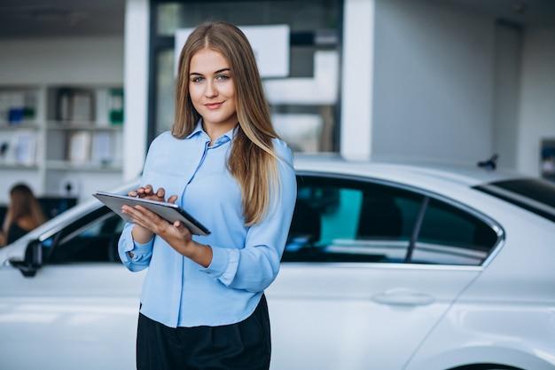 Vendedor femenino en una sala de exposición de automóviles junto al automóvil