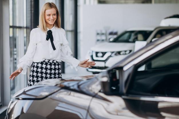 Vendedor femenino en una sala de exposición de automóviles de pie junto al coche