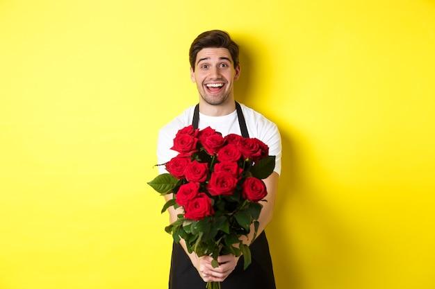 Vendedor en floristería vistiendo delantal negro, dando ramo de rosas y sonriendo, de pie sobre la pared amarilla
