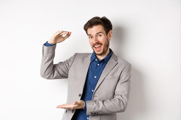 Vendedor guapo en traje mostrando gran tamaño, grandes ingresos, sonriendo a la cámara con entusiasmo, de pie sobre fondo blanco.