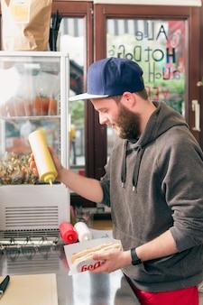 Vendedor haciendo hotdog en snack bar de comida rápida