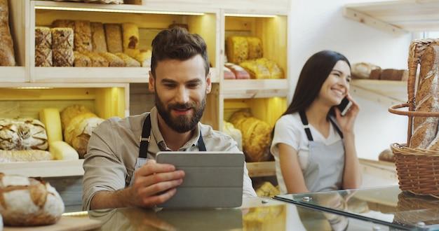 Vendedor de hombre caucásico con tableta mientras está de pie en el mostrador de la panadería, su compañera de trabajo hablando por teléfono detrás de él. dentro