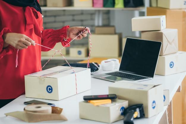 El vendedor en línea trabaja en la oficina en casa y empaca la caja de envío al cliente.