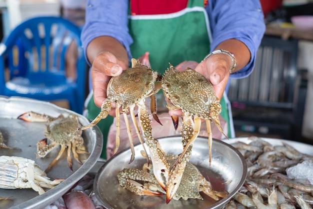 El vendedor local de mariscos sostiene y muestra dos agarres. tienda de mariscos local en tailandia.