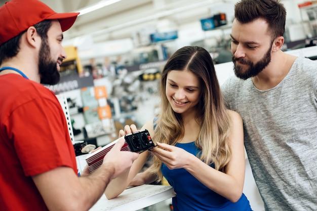El vendedor está mostrando la herramienta eléctrica a los clientes
