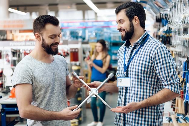 El vendedor está mostrando las llaves inglesas nuevas del cliente barbudo en tienda.