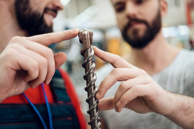 Vendedor está mostrando un nuevo taladro gigante al cliente