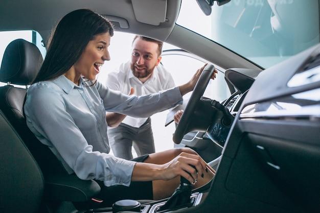 Vendedor y mujer en busca de un automóvil en una sala de exposición de automóviles.
