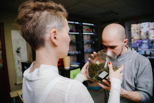 El vendedor ofrece oler té al cliente.