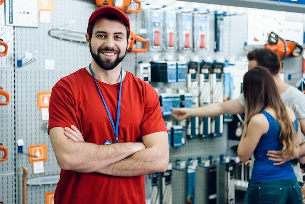 Vendedor posa en la tienda de herramientas eléctricas