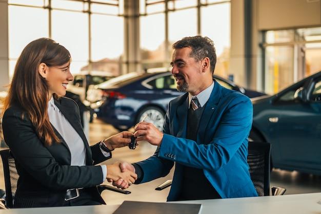 Vendedor que da llaves del coche mientras que sacude la mano de una mujer en un salón del coche.
