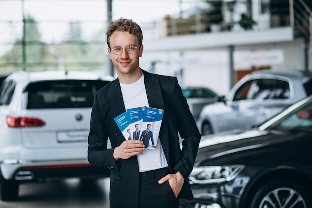 Vendedor en una sala de exposición de automóviles con volantes de negocios.
