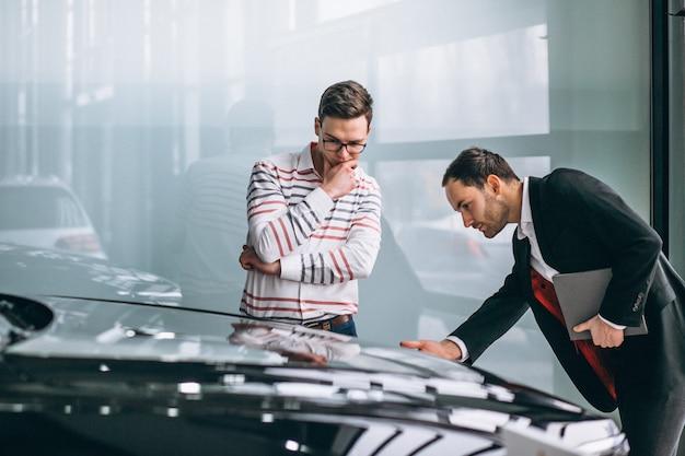 Vendedor en una sala de exposición de coches vendiendo un coche.