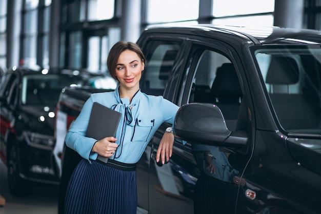 Vendedor de sexo femenino en una sala de exposición del coche