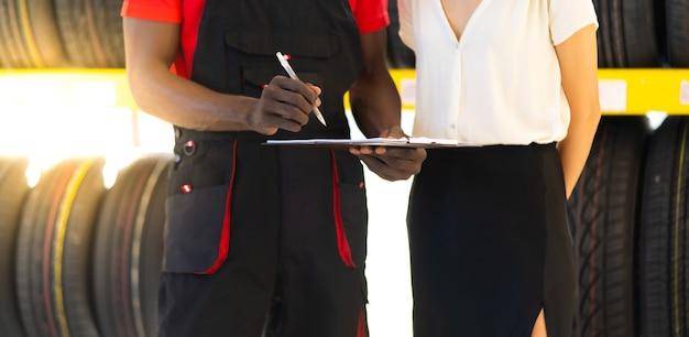 Vendedor de sexo masculino negro que muestra los neumáticos de la rueda al cliente de la mujer caucásica en el servicio de reparación de automóviles y la tienda de la tienda de automóviles.