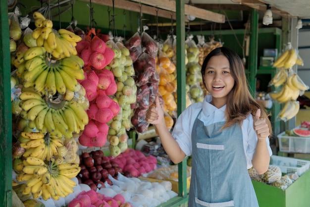 Vendedor sonriente joven en delantal felizmente con los pulgares hacia arriba en el puesto de frutas