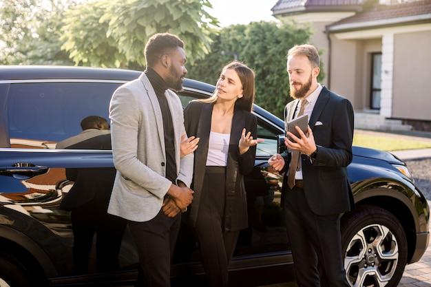 Vendedor con tableta y clientes, pareja de negocios, mujer caucásica y hombre africano, de pie cerca de un coche nuevo al aire libre. gente de negocios usando tableta de pie cerca del coche negro al aire libre