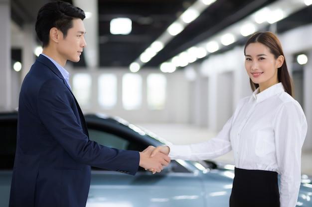 Vendedora asiática en apretón de manos de negocio automático con hombre