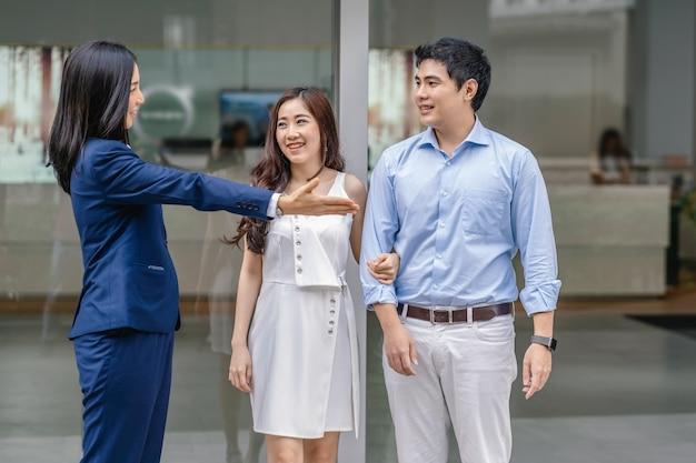 La vendedora asiática da la bienvenida al cliente de la pareja para que revise el automóvil frente a la sala de exhibición.