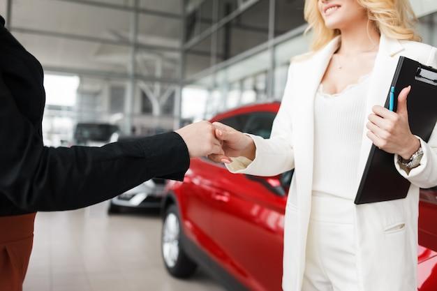 La vendedora de autos le da la mano a un cliente en primer plano