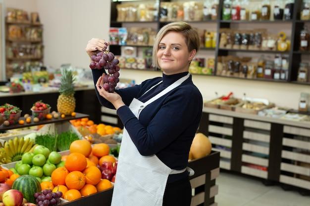Vendedora ayuda a un cliente a comprar frutas y verduras