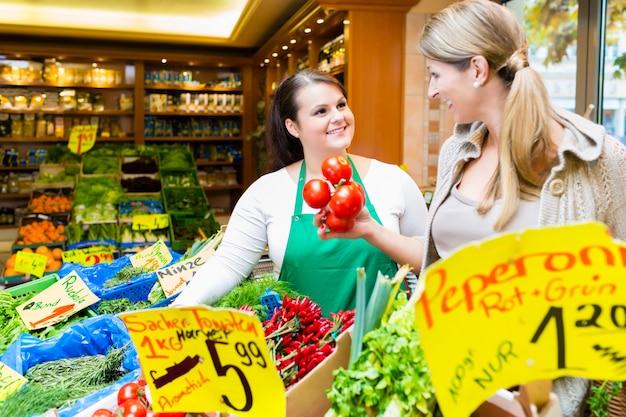Vendedora ayudando a una mujer a comprar comestibles.