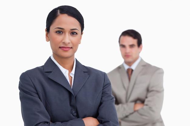 Vendedora con los brazos cruzados y un colega detrás de ella